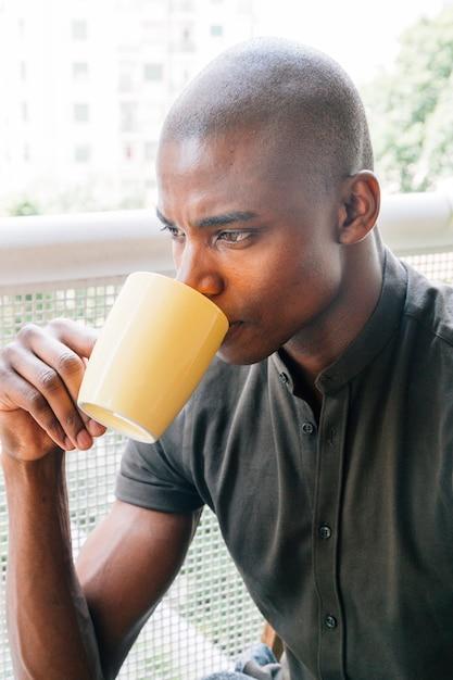 Primo piano di un giovane uomo africano rasato che beve il caffè Foto Gratuite