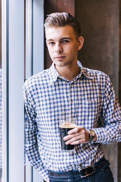Primo piano di un giovane uomo bello tenendo i bicchieri da birra guardando la fotocamera Foto Gratuite