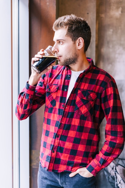 Primo piano di un giovane uomo con la mano in tasca a bere i bicchieri di birra Foto Gratuite