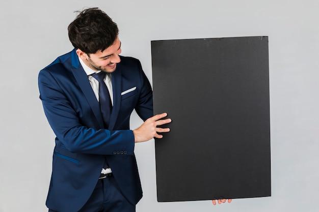 Primo piano di un giovane uomo d'affari che tiene cartello nero bianco su sfondo grigio Foto Gratuite