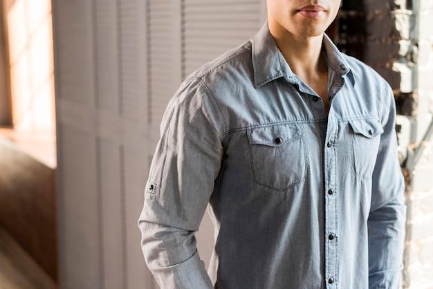 Primo piano di un giovane uomo in camicia di jeans blu Foto Gratuite