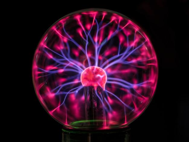 Primo piano di un globo al plasma nell'oscurità Foto Gratuite