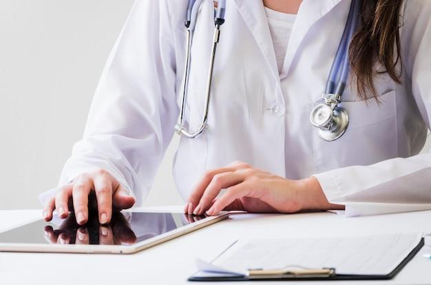 Primo piano di un medico femminile che utilizza compressa digitale e rapporto medico sullo scrittorio Foto Gratuite