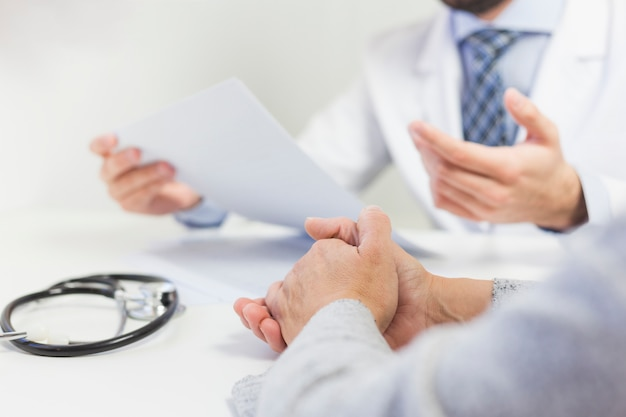 Primo piano di un medico nel suo ufficio discutendo la relazione medica con il paziente Foto Gratuite