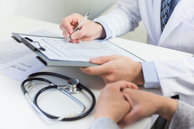 Primo piano di un medico riempiendo il modulo medico con il paziente Foto Gratuite