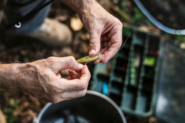 Primo piano di un pescatore che mette esca Foto Premium
