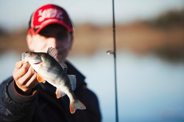 Primo piano di un pescatore che tiene il pesce fresco Foto Gratuite