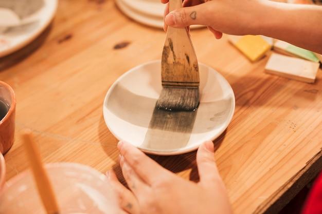 Primo piano di un piatto della ceramica della pittura della mano della donna con il pennello sullo scrittorio di legno Foto Gratuite