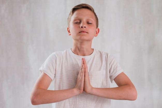 Primo piano di un ragazzo che chiude i suoi occhi facendo meditazione contro il muro di cemento Foto Gratuite