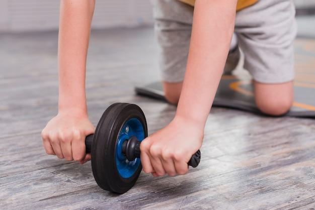 Primo piano di un ragazzo che si inginocchia esercitandosi con lo scorrevole del rullo Foto Gratuite