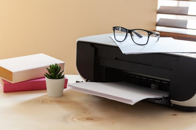 Primo piano di un tavolo da ufficio con stampante su di esso Foto Premium