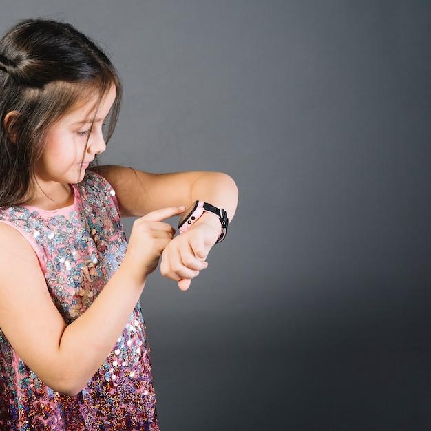 Primo piano di un tempo di sorveglianza della ragazza sull'orologio contro fondo grigio Foto Gratuite