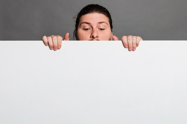 Primo piano di un uomo che dà una occhiata dietro la carta di carta bianca contro fondo grigio Foto Gratuite