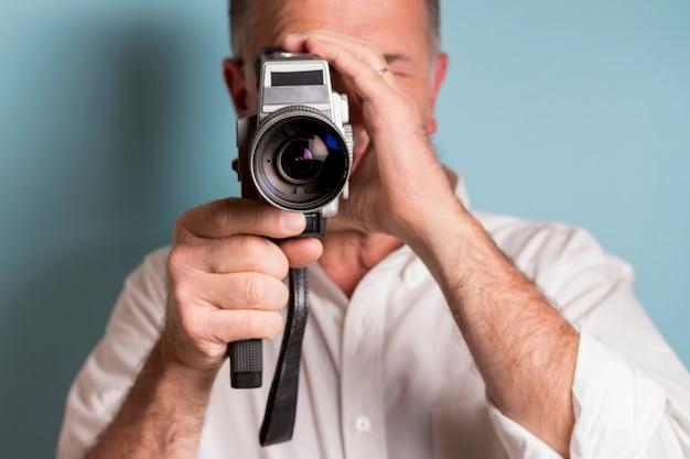 Primo piano di un uomo che guarda attraverso la macchina da presa di 8mm contro il contesto blu Foto Gratuite
