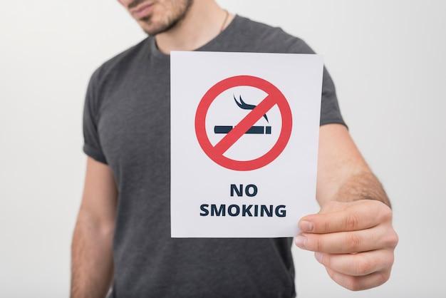 Primo piano di un uomo che mostra il segno non fumatori contro fondo bianco Foto Gratuite