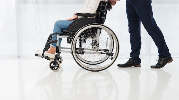 Primo piano di un uomo che spinge la donna che si siede sulla sedia a rotelle Foto Gratuite