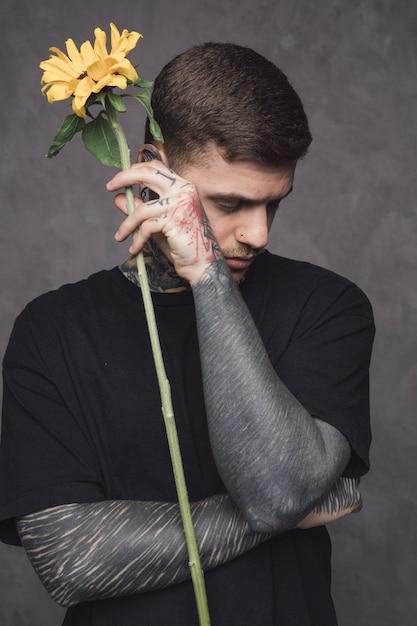 Primo piano di un uomo con il tatuaggio nella sua mano che tiene girasole in mano contro il muro Foto Gratuite