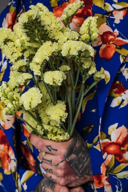 Primo piano di un uomo con il tatuaggio sulla sua mano che tiene il fiore di limonium in mano Foto Gratuite