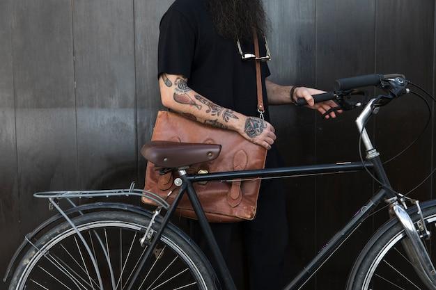 Primo piano di un uomo con la sua borsa e bicicletta davanti al muro nero Foto Gratuite