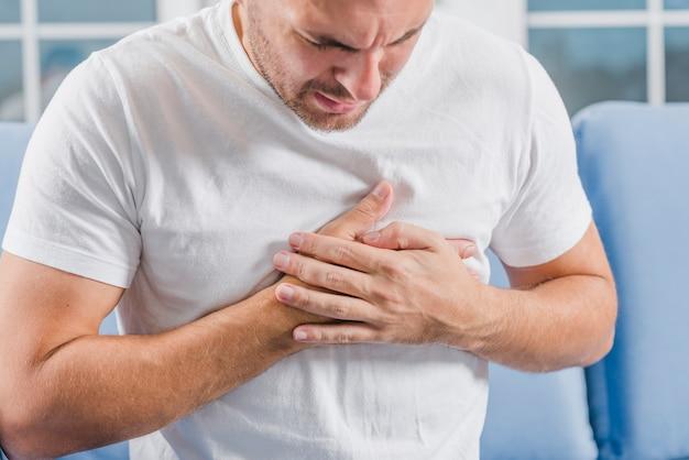 Primo piano di un uomo con sintomi di attacco di cuore che tocca il suo cuore con due mani Foto Gratuite