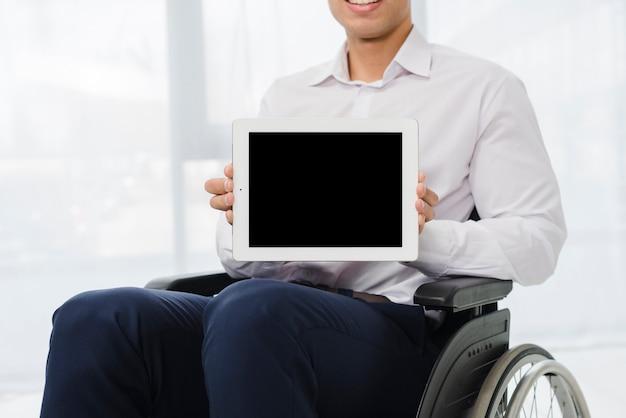 Primo piano di un uomo d'affari che si siede sulla sedia a rotelle che mostra compressa digitale con lo schermo nero Foto Gratuite