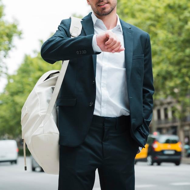 Primo piano di un uomo d'affari con lo zaino bianco sulla sua spalla guardando il tempo sulla strada Foto Gratuite