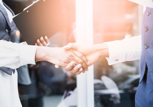 Primo piano di un uomo d'affari e la mano della donna di affari che agitano le mani all'aperto Foto Gratuite