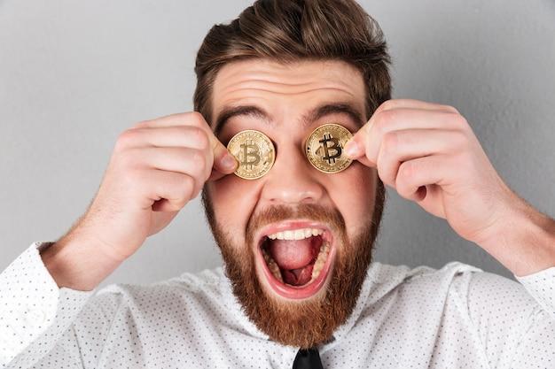 Primo piano di un uomo d'affari gioioso con bitcoin nei suoi occhi Foto Gratuite