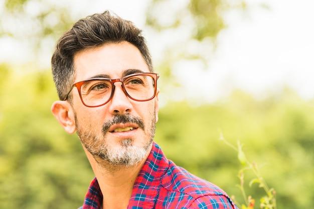 Primo piano di un uomo in occhiali rossi guardando lontano Foto Gratuite