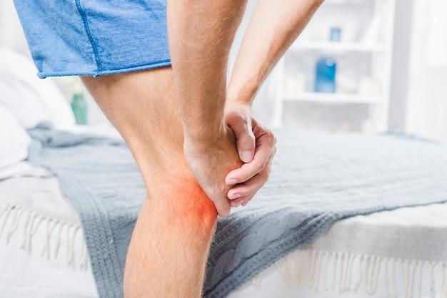 Primo piano di un uomo in piedi vicino al letto che soffre di dolore al ginocchio Foto Gratuite