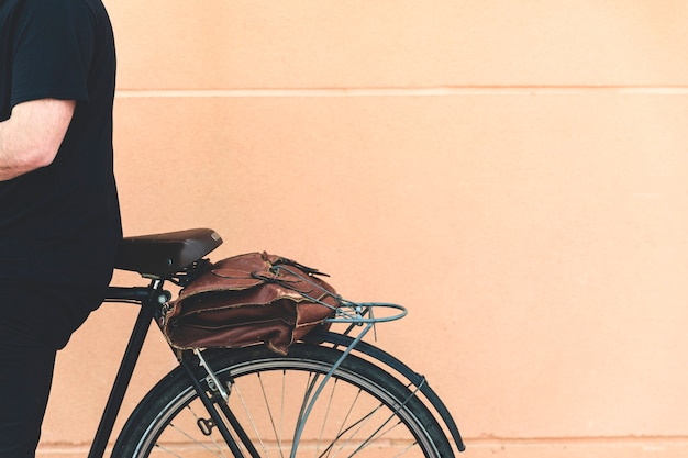 Primo piano di un uomo seduto sulla bicicletta contro il muro beige Foto Gratuite