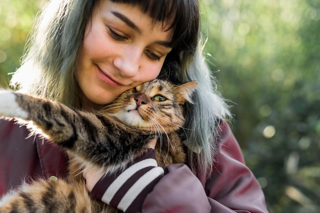 Primo piano di una bella donna sorridente che abbraccia il suo gatto soriano in giardino Foto Gratuite