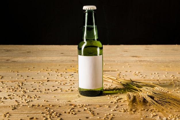 Primo piano di una bottiglia alcolica e spighe di grano sulla plancia di legno Foto Gratuite