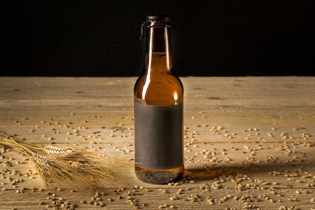 Primo piano di una bottiglia da birra e spighe di grano su venatura del legno Foto Gratuite