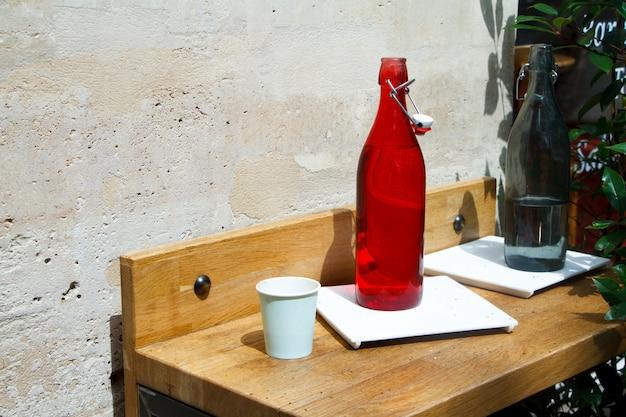 Primo piano di una bottiglia di acqua rossa e vetro su un tavolo del ristorante contro un muro di pietra leggera Foto Premium