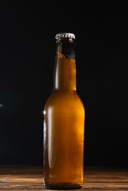 Primo piano di una bottiglia di birra sulla scrivania in legno Foto Gratuite