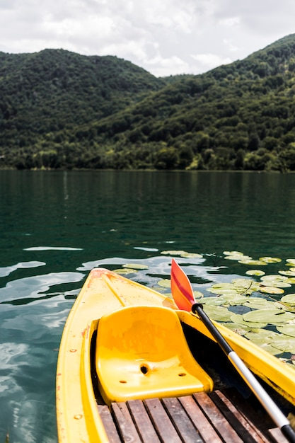 Primo piano di una canoa vuota sul lago vicino alla montagna Foto Gratuite