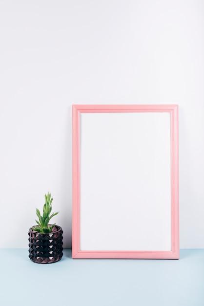 Primo piano di una cornice vuota con una piccola pianta in vaso sulla scrivania blu Foto Gratuite
