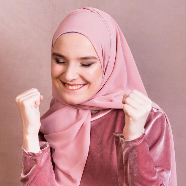 Primo piano di una donna che celebra il suo successo con il pugno di serraggio Foto Gratuite