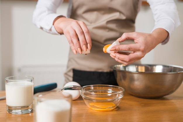Primo piano di una donna che mette il tuorlo d'uovo nella ciotola di vetro Foto Gratuite