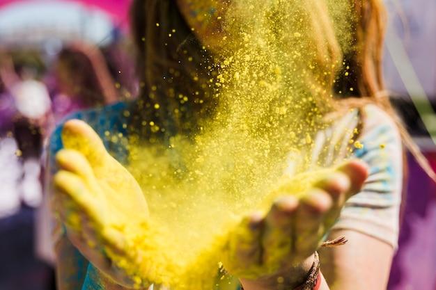 Primo piano di una donna che spolvera il colore giallo di holi Foto Gratuite