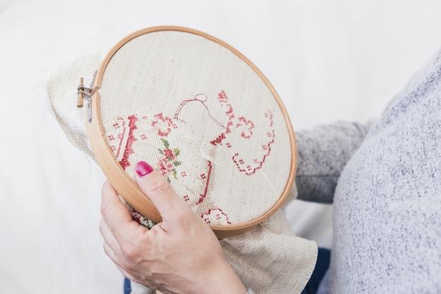 Primo piano di una donna croce cucitura sul cerchio Foto Gratuite