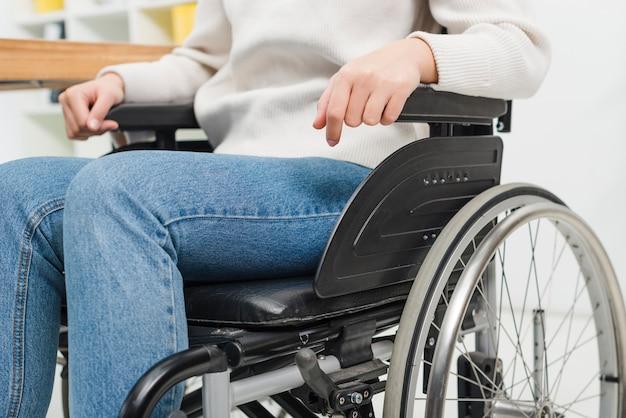 Primo piano di una donna disabile che si siede sulla sedia a rotelle Foto Gratuite