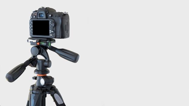 Primo piano di una fotocamera dslr su un treppiede su sfondo bianco Foto Gratuite