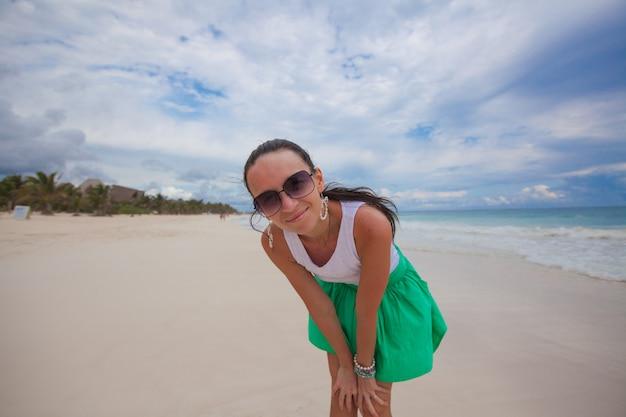 Primo piano di una giovane bella donna sulla spiaggia esotica bianca Foto Premium