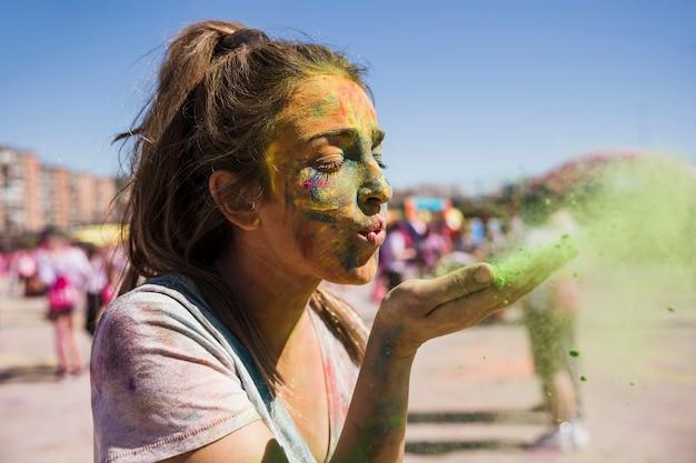 Primo piano di una giovane donna che soffia colore holi Foto Gratuite