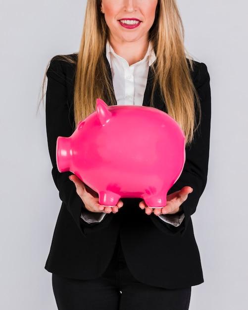 Primo piano di una giovane donna di affari sorridente che tiene porcellino salvadanaio ceramico rosa a disposizione Foto Gratuite