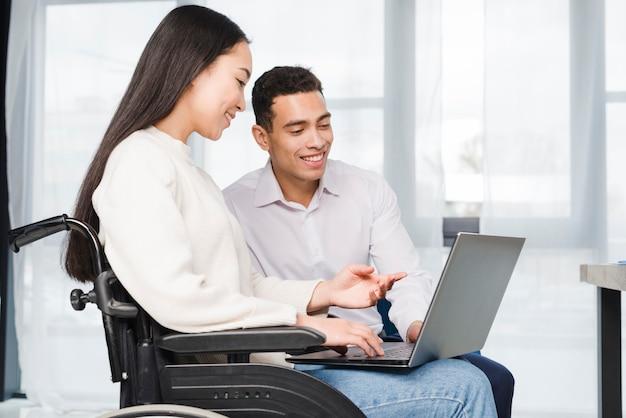 Primo piano di una giovane donna sorridente che si siede sulla sedia a rotelle che mostra al suo collega sul computer portatile Foto Gratuite