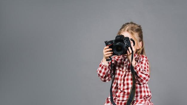 Primo piano di una macchina fotografica della tenuta della ragazza davanti al suo fronte che sta contro il contesto grigio Foto Gratuite
