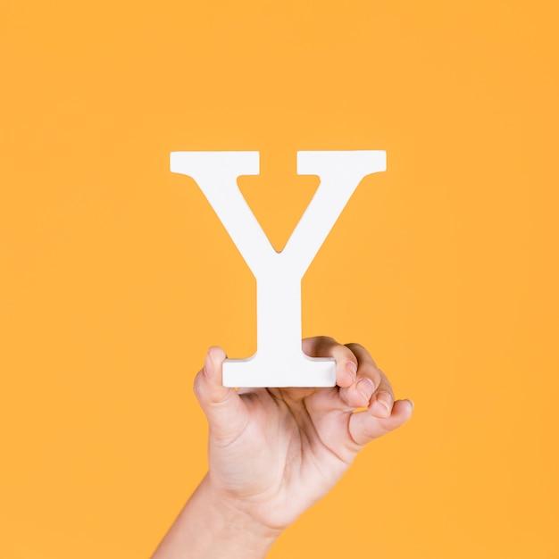 Primo piano di una mano che regge l'alfabeto y su sfondo Foto Gratuite